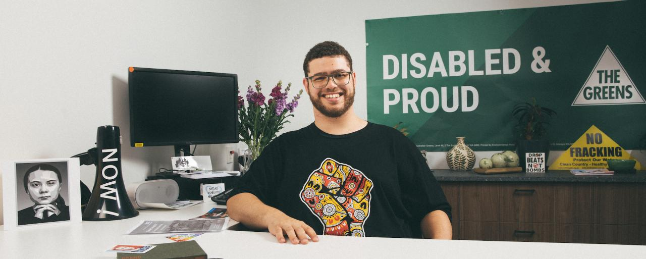Greens Senator Jordon Steele-John wearing a black shirt with a yellow and red logo. Sitting behind a white desk. Behind Jordon is a banner that says Disabled and Proud with a Greens logo