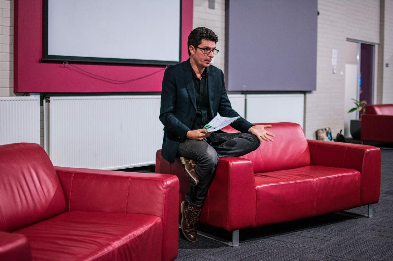 Scott Ludlam talks to the audience, sitting on a red couch